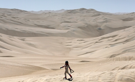 Erik Wevers, Dutch co-driver of the Mitsubishi driven by Fabian Lurquin, from Belgium, walks along the desert after their car got stuck in the sand during the 12th stage of the 2012 Argentina-Chile-Peru Dakar Rally between Arequipa and Nazca in Peru, Jan. 13, 2012. (AP Photo/Martin Mejia)