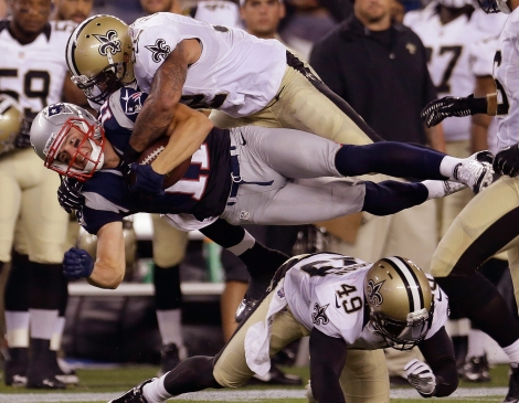 New England Patriots wide receiver Julian Edelman (11) is hit by New Orleans Saints linebacker Jonathan Casillas (52) as they sail over Saints defensive back Marquis Johnson (49) during their first NFL preseason football game in Foxborough, Mass., Thursday, Aug. 9, 2012. (AP Photo/Elise Amendola)