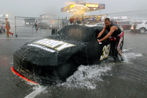 Crew members push Ryan Newman's car in a downpour that shortened the NASCAR Sprint Cup Series auto race, Sunday, Aug. 5, 2012, at Pocono Raceway in Long Pond, Pa. Jeff Gordon won. (AP Photo/Mel Evans)