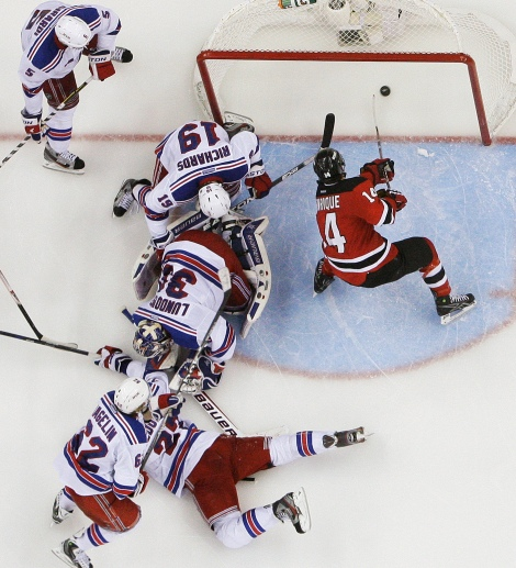 New Jersey Devils' Adam Henrique (14) scores during the overtime of Game 6 of the NHL hockey Stanley Cup Eastern Conference finals, as New York Rangers' Henrik Lundqvist (30), Brad Richards (19), and Carl Hagelin (62) defend, Friday, May 25, 2012, in Newark, N.J. The Devils won 3-2. (AP Photo/Frank Franklin II)