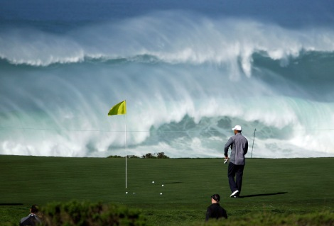 Tiger Woods walks to his ball on the 15th green of the Monterey Peninsula Country Club shore course as waves crash in the background during a practice round at the AT&T Pebble Beach National Pro-Am PGA Tour golf tournament in Pebble Beach, Calif., Wednesday, Feb. 8, 2012. (AP Photo/Eric Risberg)
