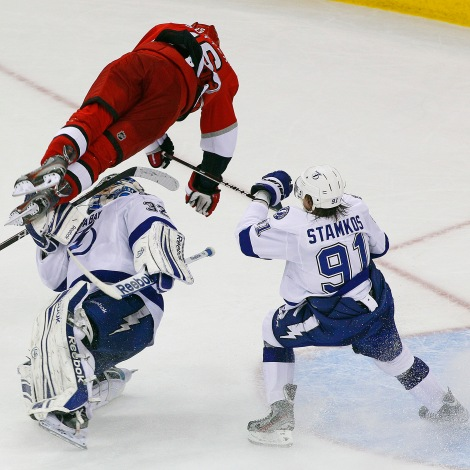 Carolina Hurricanes' Brandon Sutter (16) collides with Tampa Bay Lightning goalie Mathieu Garon (32) as Lightning's' Steven Stamkos (91) watches during the third period of an NHL hockey game in Raleigh, N.C., Saturday, March 3, 2012. Tampa Bay won 4-3 in overtime. (AP Photo/Karl B DeBlaker)