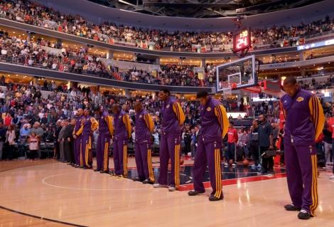 Luci ridotte e Los Angeles Lakers a testa bassa durante il minuto di silenzio in campo a Washington, prima della sfida vinta contro i Wizards (Foto AP/Alex Brandon)