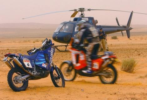 Un partecipante passa accanto alla moto di Fabrizio Meoni mentre lo sfortunato pilota italiano viene portato via dall'elicottero sullo sfondo dopo la caduta che l'ha ucciso l'11 gennaio 2005 (AP Photo/Bernard Papon, Presse Sports)