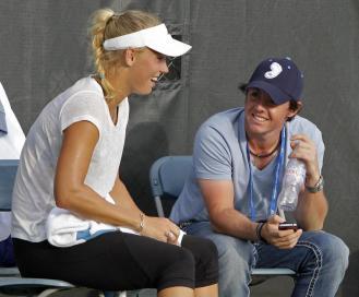 Rory McIlroy chiacchiera con Caroline Wozniacki durante una pausa degli allenamenti di tennis della danese (Foto AP/Al Behrman)
