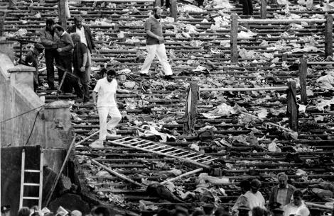 Spettatori camminano tra quel che resta del settore Z, dopo il crollo che portò alla morte di 39 tifosi (AP Photo)